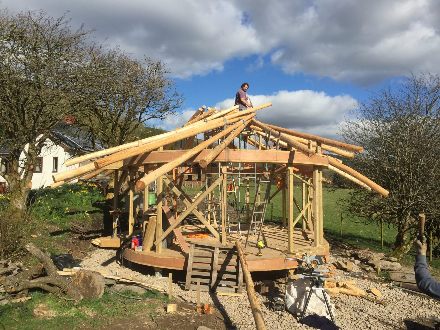 Ty Mam Mawr straw bale roundhouse in skeleton form with the reciprocal frame roof about half completed
