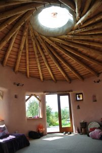 Inside the straw bale roundhouse with a great view of the central skylight and reciprocating frame roof