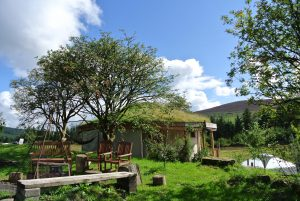 The straw bale roundhouse and central fire pit at Ty Mam Mawr off grid eco retreat centre