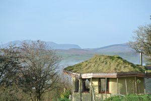 The straw bale roundhouse at Ty Mam Mawr off grid eco retreat centre with Arenig Fawr and Snowdonia National Park in the background